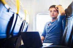 Homem novo considerável a bordo de um avião Fotos de Stock