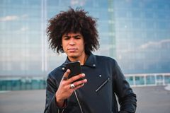 Homem novo considerável com cabelo afro usando um telefone esperto e olhando sério, fundo da cidade imagem de stock royalty free