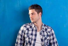 Homem novo considerável com a camisa de manta no azul imagem de stock royalty free