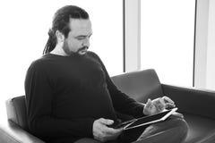 Homem novo considerável com dreadlocks usando seu PC digital da tabuleta em uma sala de estar do aeroporto, sala de espera modern Imagem de Stock