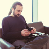 Homem novo considerável com dreadlocks usando seu telefone em uma sala de estar do aeroporto com luminoso Imagem de Stock Royalty Free