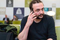 Homem novo considerável com dreadlocks usando seu telefone em uma sala de estar do aeroporto com luminoso Fotografia de Stock Royalty Free
