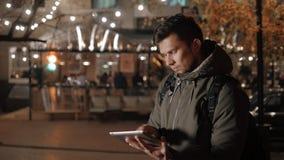 Homem novo considerável com PC da tabuleta que navega nas ruas da noite Foto de Stock