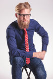 Homem novo considerável da forma que senta-se em um tamborete quando Fotografia de Stock Royalty Free