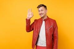 Homem novo considerável de sorriso da moda do retrato 25-30 anos no casaco de cabedal vermelho, posição do t-shirt isolado em bri foto de stock royalty free
