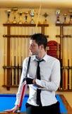 Homem novo considerável do bilhar com sugestão e laço da camisa Foto de Stock Royalty Free