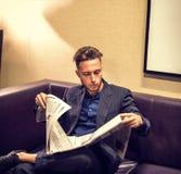 Homem novo considerável em casa que lê o jornal fotografia de stock royalty free