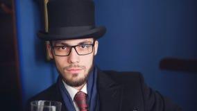Homem novo considerável em um uísque bebendo do terno clássico no restaurante filme