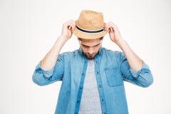 Homem novo considerável na camisa azul que põe sobre o chapéu Foto de Stock