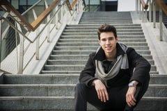 Homem novo considerável na moda que senta-se em uma escadaria longa fora Foto de Stock