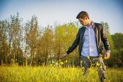 Homem novo considerável no campo, no campo ou Fotografia de Stock