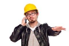 Homem novo considerável no capacete de segurança no telefone imagem de stock royalty free