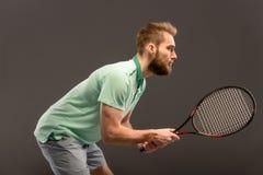 Homem novo considerável no polo que guarda o tênis Fotografia de Stock Royalty Free