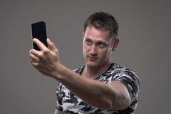 Homem novo considerável no t-shirt do teste padrão da camuflagem que toma fotos com telefone celular foto de stock royalty free