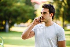 Homem novo considerável no talkig do parque em seu telefone fotos de stock