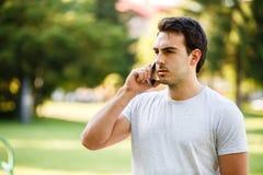 Homem novo considerável no talkig do parque em seu telefone imagens de stock