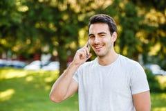 Homem novo considerável no talkig do parque em seu telefone imagem de stock royalty free
