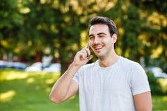Homem novo considerável no talkig do parque em seu telefone fotos de stock royalty free