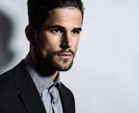 Homem novo considerável no terno no fundo cinzento fotografia de stock