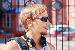 Homem novo considerável nos óculos de sol e nos fones de ouvido Fotografia de Stock