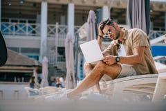 homem novo considerável nos óculos de sol usando o portátil ao descansar no chaise imagem de stock royalty free