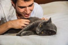 Homem novo considerável que afaga seu Gray Cat Pet imagens de stock
