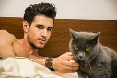 Homem novo considerável que afaga seu Gray Cat Pet fotografia de stock royalty free