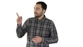 Homem novo considerável que anda e que olha à câmera e que aponta aos lados que mostram algo no fundo branco foto de stock