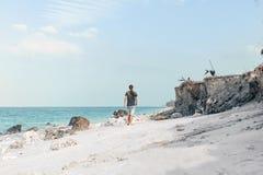 Homem novo considerável que anda na praia Foto de Stock