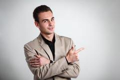 Homem novo considerável que aponta no copyspace com sua mão, retrato fotografia de stock