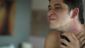 Homem novo considerável que barbeia com a lâmina elétrica no banheiro perto do espelho video estoque