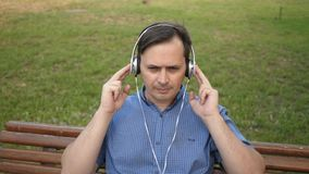 Homem novo considerável que descansa em um parque que escuta a música de seu smartphone com fones de ouvido e que dança fora na vídeos de arquivo