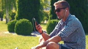 Homem novo considerável que escuta a música vídeos de arquivo