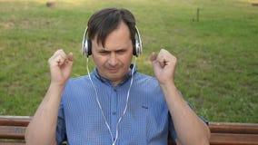 Homem novo considerável que escuta a música de seu smartphone com os fones de ouvido, dançando fora no parque em um banco no filme