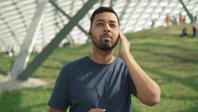 Homem novo considerável que escuta sua música favorita com fones de ouvido filme