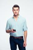 Homem novo considerável que está com smartphone Imagem de Stock Royalty Free