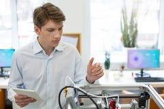 Homem novo considerável que estuda o mecanismo da impressora 3D Foto de Stock