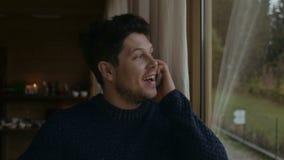 Homem novo considerável que fala no telefone celular e no sorriso filme