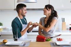 Homem novo considerável que faz o gracejo de pedir que sua amiga case-se com uma pimenta de sino na cozinha em casa fotos de stock royalty free