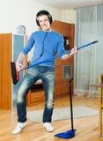 Homem novo considerável que finge jogar a guitarra com vassoura Fotografia de Stock Royalty Free