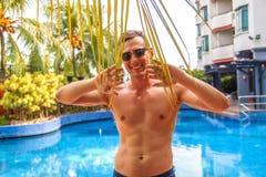 Homem novo considerável que inclina-se na borda da piscina e que sorri na câmera em um clima tropical fotos de stock