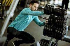 Homem novo considerável que prepara pesos no gym imagem de stock