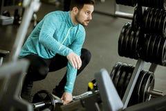 Homem novo considerável que prepara pesos no gym foto de stock