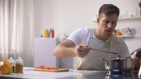 Homem novo considerável que prova a sopa vegetal, cozinhando o alimento saudável do vegetariano video estoque