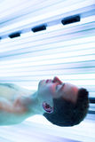 Homem novo considerável que relaxa em um solário Foto de Stock Royalty Free