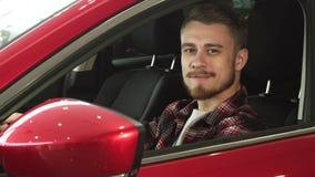 Homem novo considerável que senta-se confortavelmente em seu carro novo que sorri à câmera fotografia de stock