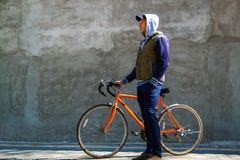 Homem novo considerável que senta-se na bicicleta e que smilling na cidade foto de stock