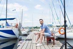 Homem novo considerável que senta-se no banco na doca da baía entre barcos homem no cais que olha afastado imagem de stock royalty free