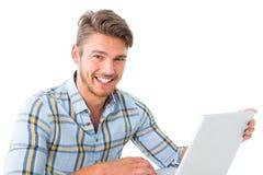 Homem novo considerável que senta-se usando o portátil imagens de stock