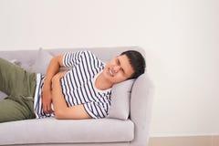 Homem novo considerável que sofre da dor de estômago ao encontrar-se sobre assim imagens de stock royalty free